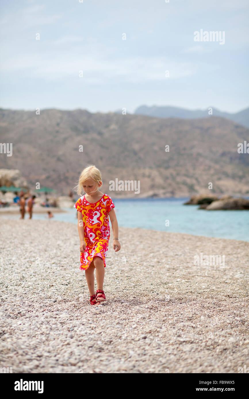 Grèce, Karpathos, Amopi, Girl (6-7) standing on beach Banque D'Images
