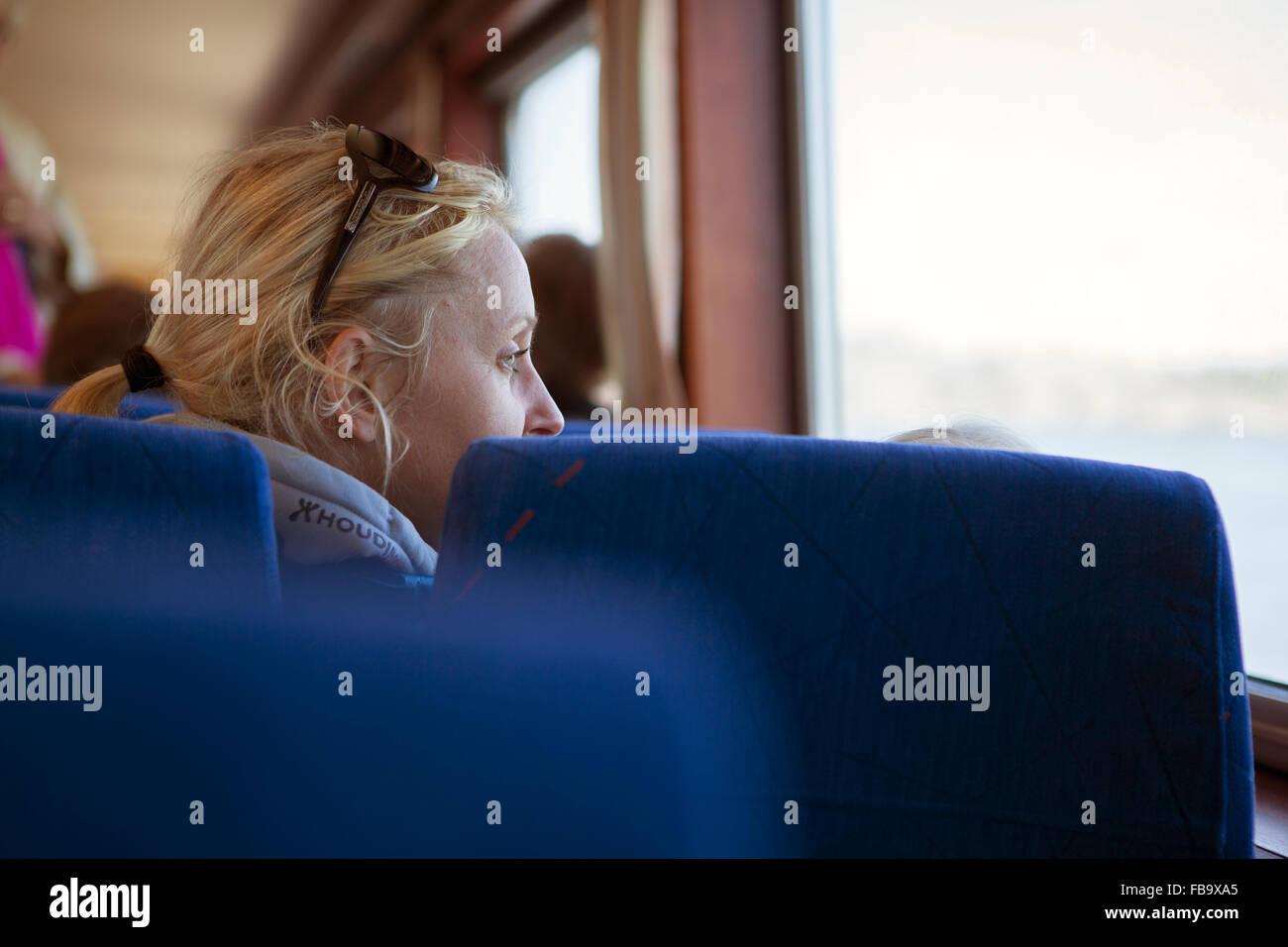 La Suède, l'archipel de Göteborg, Vastergotland, Styrso, blonde mature femme regardant par la fenêtre Photo Stock
