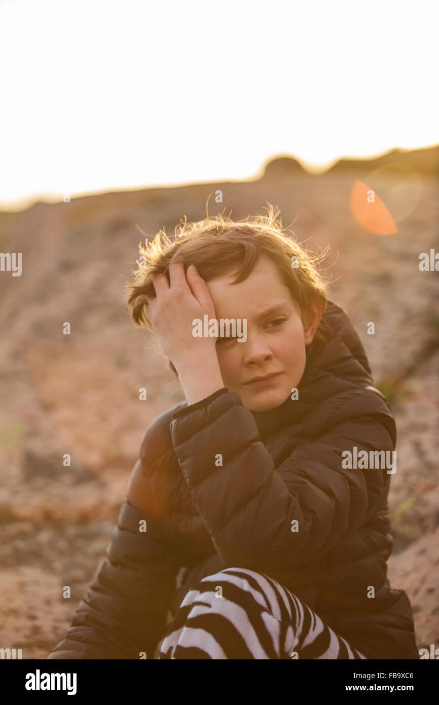 La Suède, Bohuslan, Sad boy (12-13) assis dehors au coucher du soleil Photo Stock