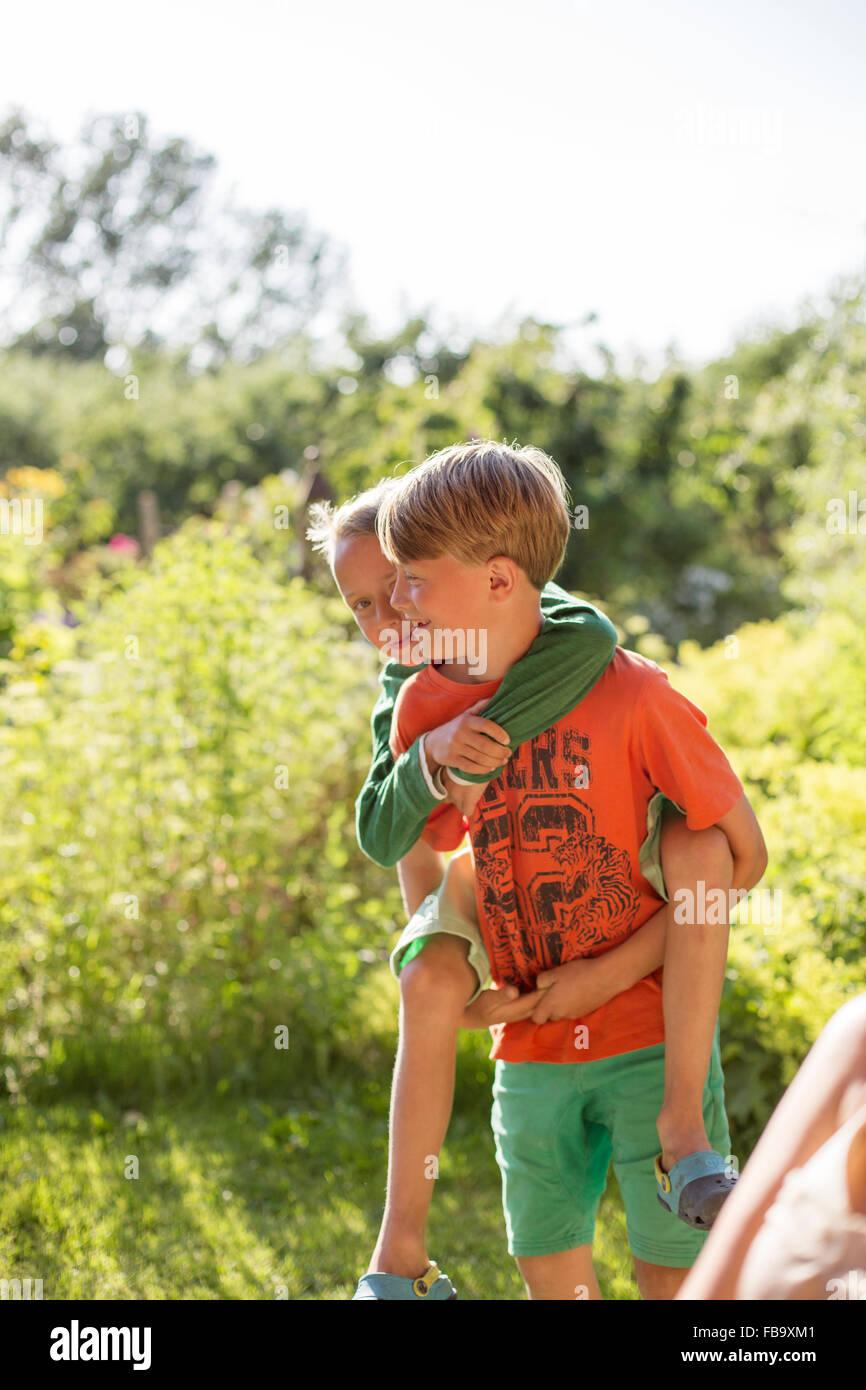 La Suède, Skane, Osterlen, Boy (10-11) donnant piggyback ride à son jeune frère (8-9) Photo Stock