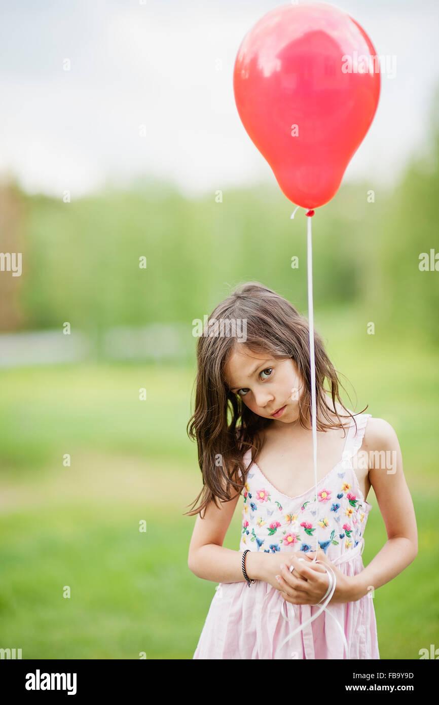 La Suède, Vastmanland, Bergslagen, cute girl (6-7) holding red balloon Photo Stock