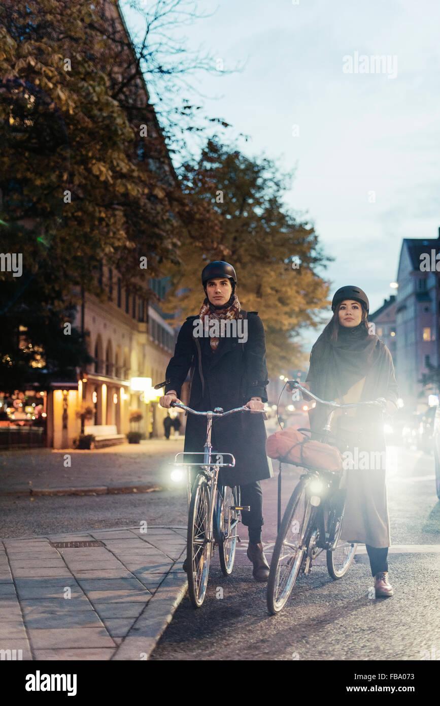 La Suède, l'Uppland, Stockholm, Vasatan, Sankt Eriksgatan, homme et femme, à vélo on city street Photo Stock