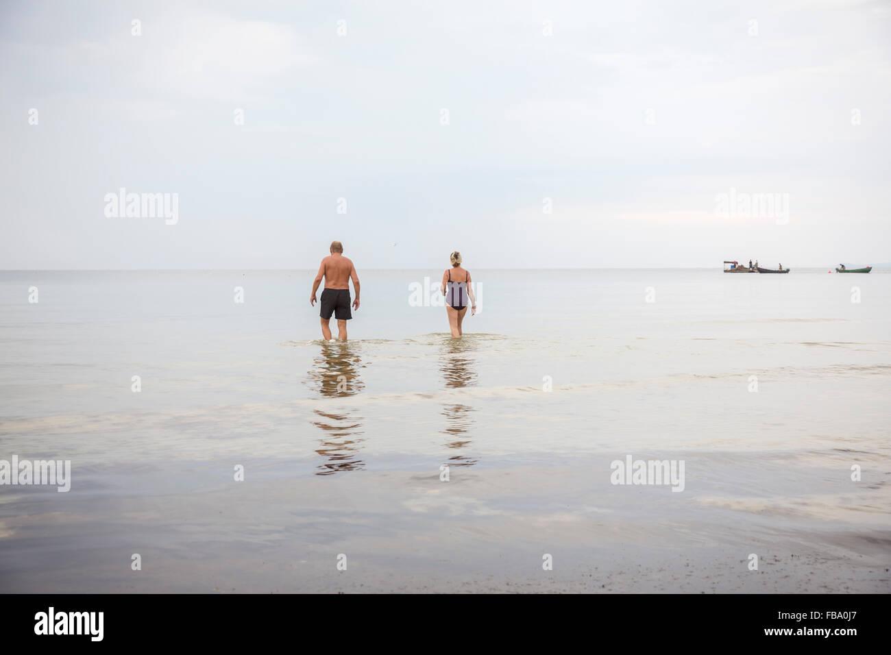 La Suède, Stockholm, l'Ahus, homme et femme, entrant dans l'eau Photo Stock