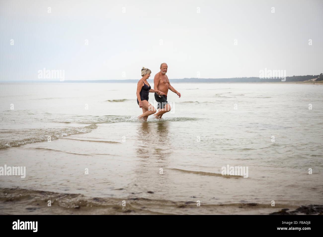 La Suède, Stockholm, l'Ahus, Senior couple pataugeant dans l'eau Photo Stock