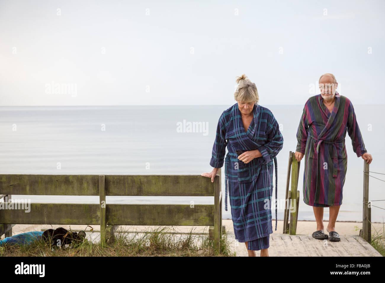 La Suède, Stockholm, l'Ahus, Senior couple revenant de la plage, dans des peignoirs Photo Stock