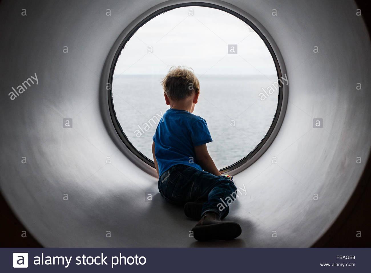 Vue arrière de boy (4-5) à l'intermédiaire de la mer Baltique à la fenêtre Photo Stock