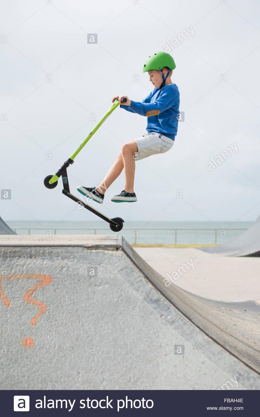 L'Australie, Queensland, Mooloolaba, jeune garçon (6-7) sur la rampe de saut sur push scooter Photo Stock