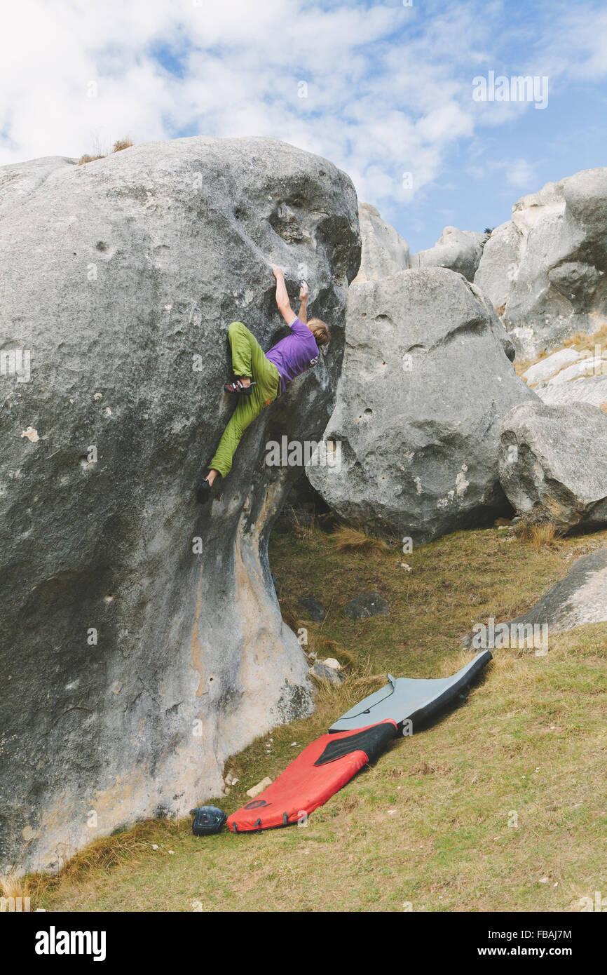 La NOUVELLE ZELANDE, Castle Hill, jeune homme grimpant boulder avec deux tampons crash préparé sous Photo Stock