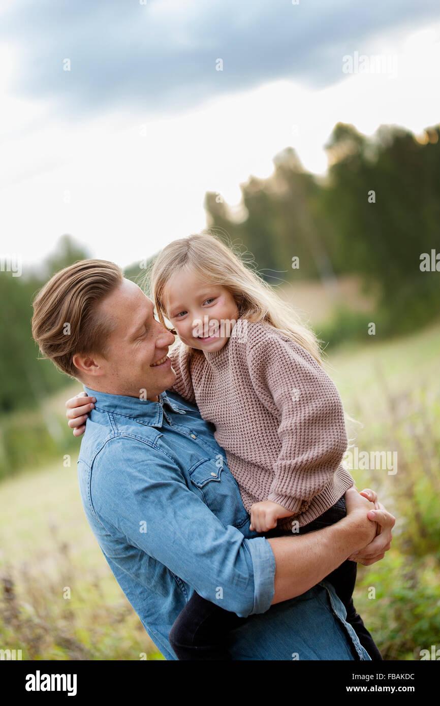 La Finlande, Uusimaa, Raasepori, Karjaa, père tenant dans les bras sa fille (6-7) Photo Stock