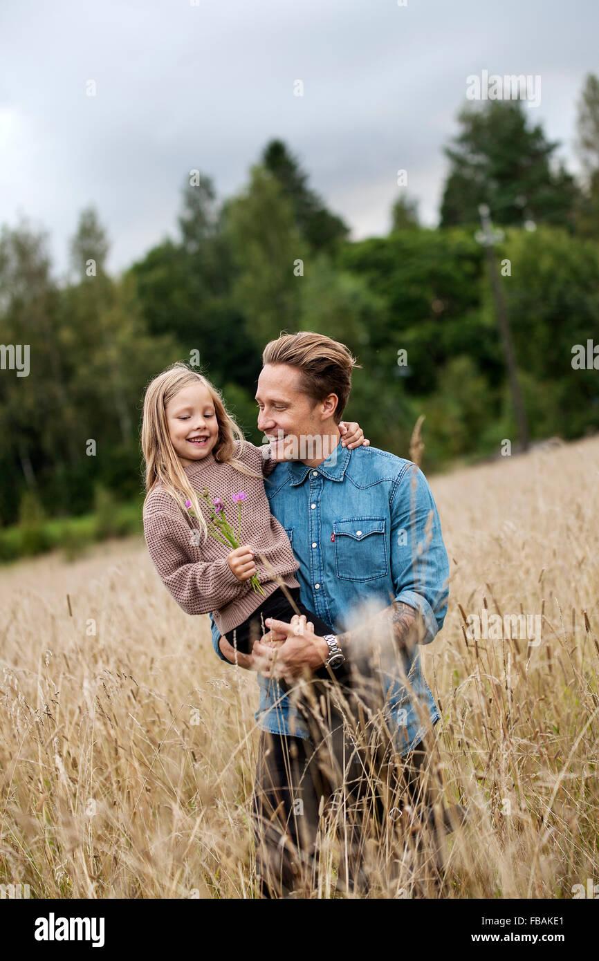 La Finlande, Uusimaa, Raasepori, Karjaa, père tenant sa fille (6-7) sur le terrain des cultures Photo Stock