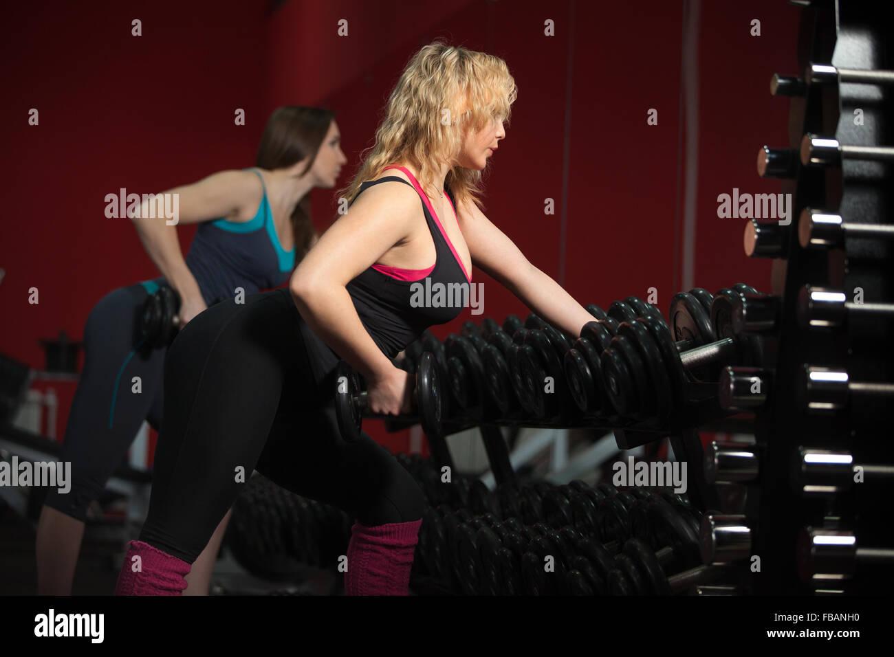 Sporty girls dans les vêtements de sport ne le culturisme exercices avec haltères en salle de sport Photo Stock