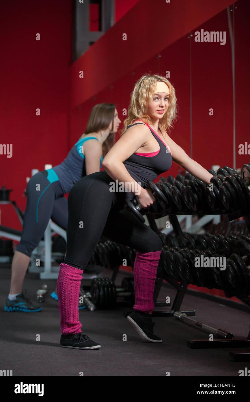 Sporty girls dans les vêtements de sport ne le culturisme exercices avec haltères en gym (regarder dans Photo Stock