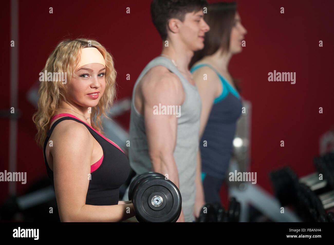 Groupe de sportifs n'exercices de musculation avec haltères en salle de sport Photo Stock