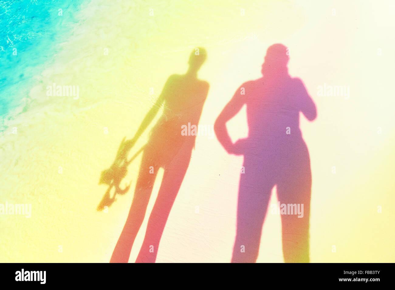 Silhouettes stylisées de femme tenant un équipement de plongée et de l'homme sur la plage. Photo Stock