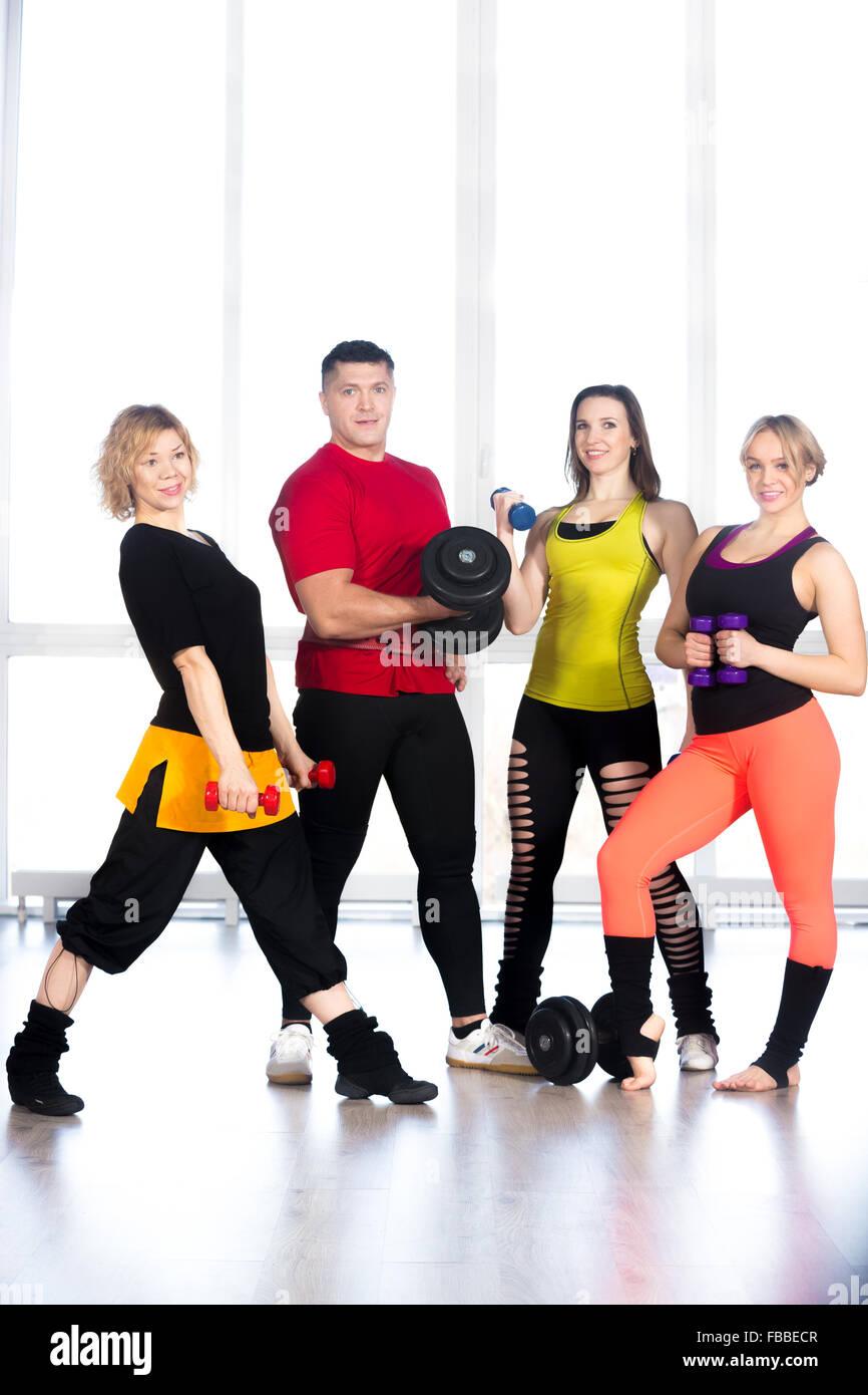 Groupe de quatre sportifs holding dumbbells de tailles différentes, faire des exercices d'haltérophilie, Photo Stock