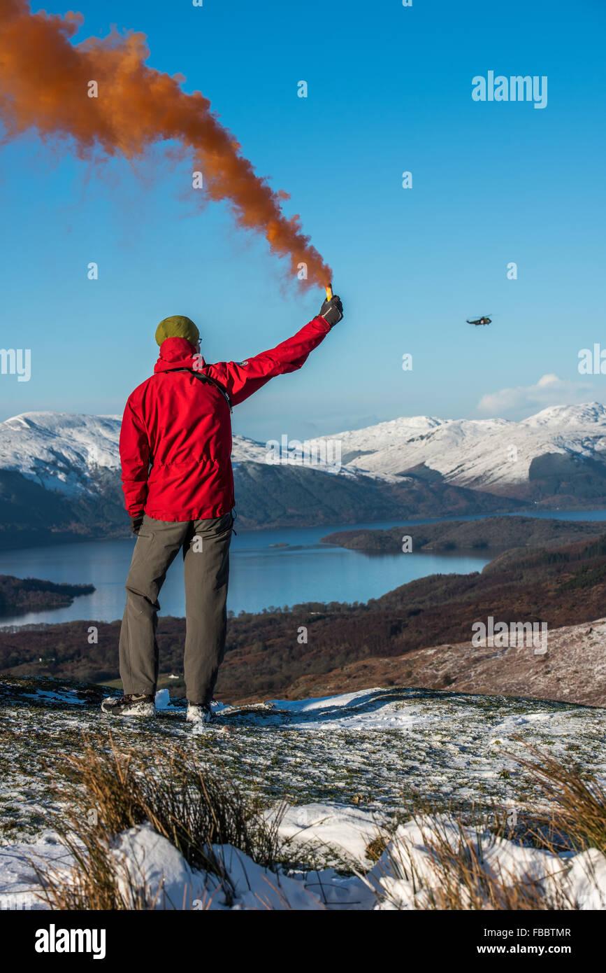 Membre de l'équipe de secours en montagne avec une torche de fumée pour attirer helicopter Banque D'Images