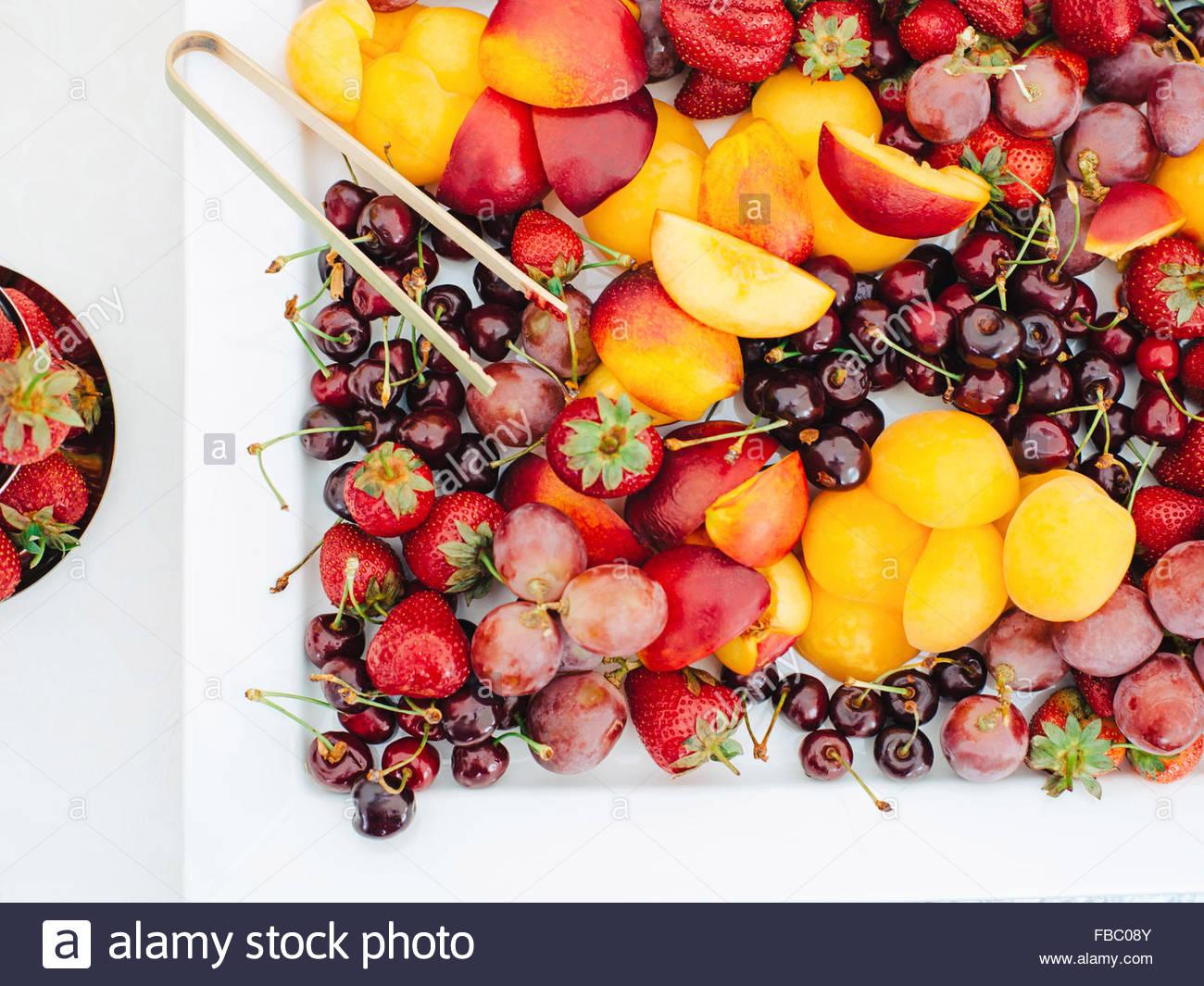 Plaque blanche avec les fruits et les baies sur une table Photo Stock