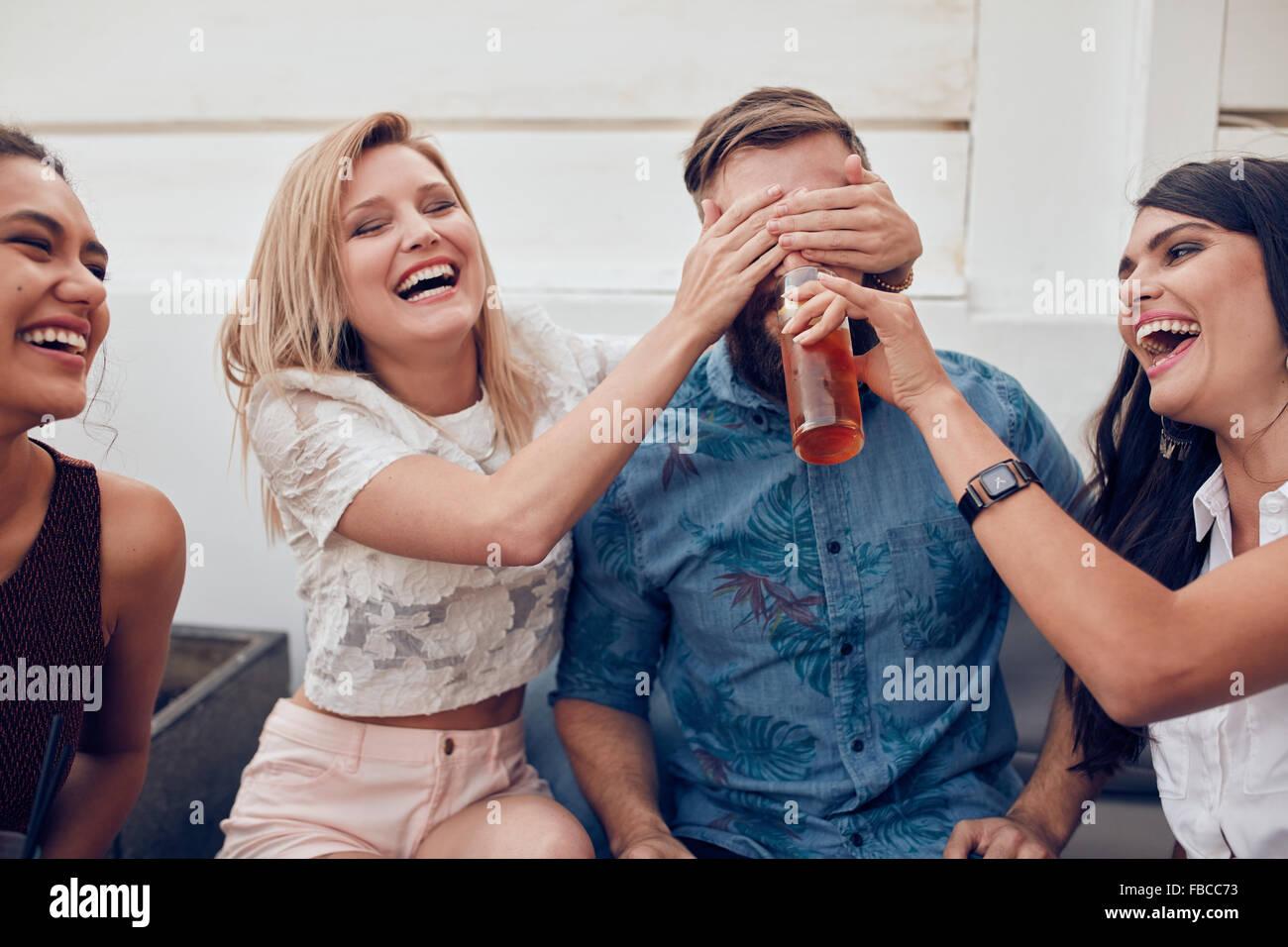 Shot de jeunes gens assis jouissant ensemble partie. Femme fermeture yeux d'un homme avec un autre donner à Photo Stock