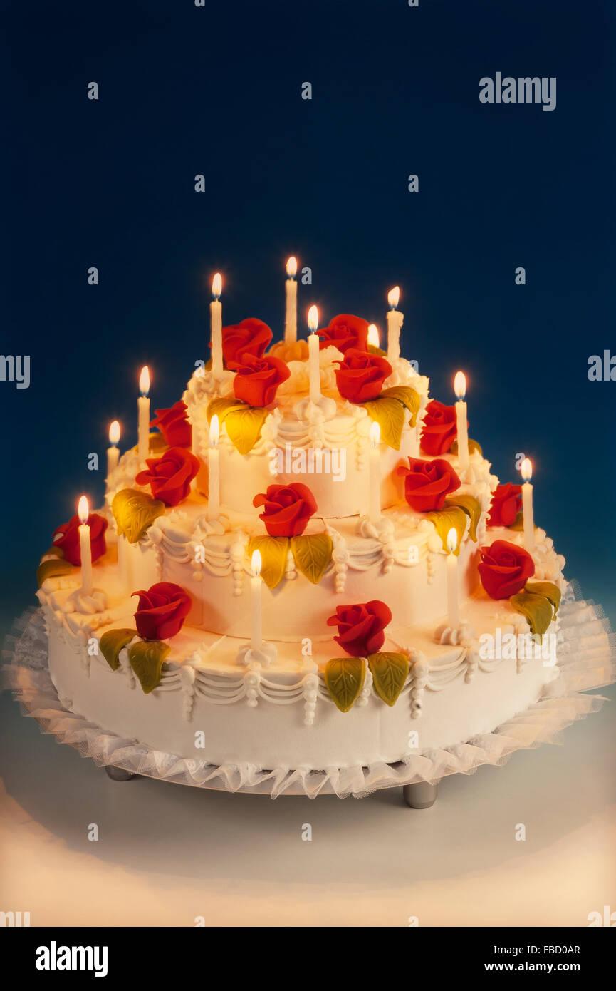 Gâteau de mariage avec des roses en massepain et allumé des bougies Photo Stock