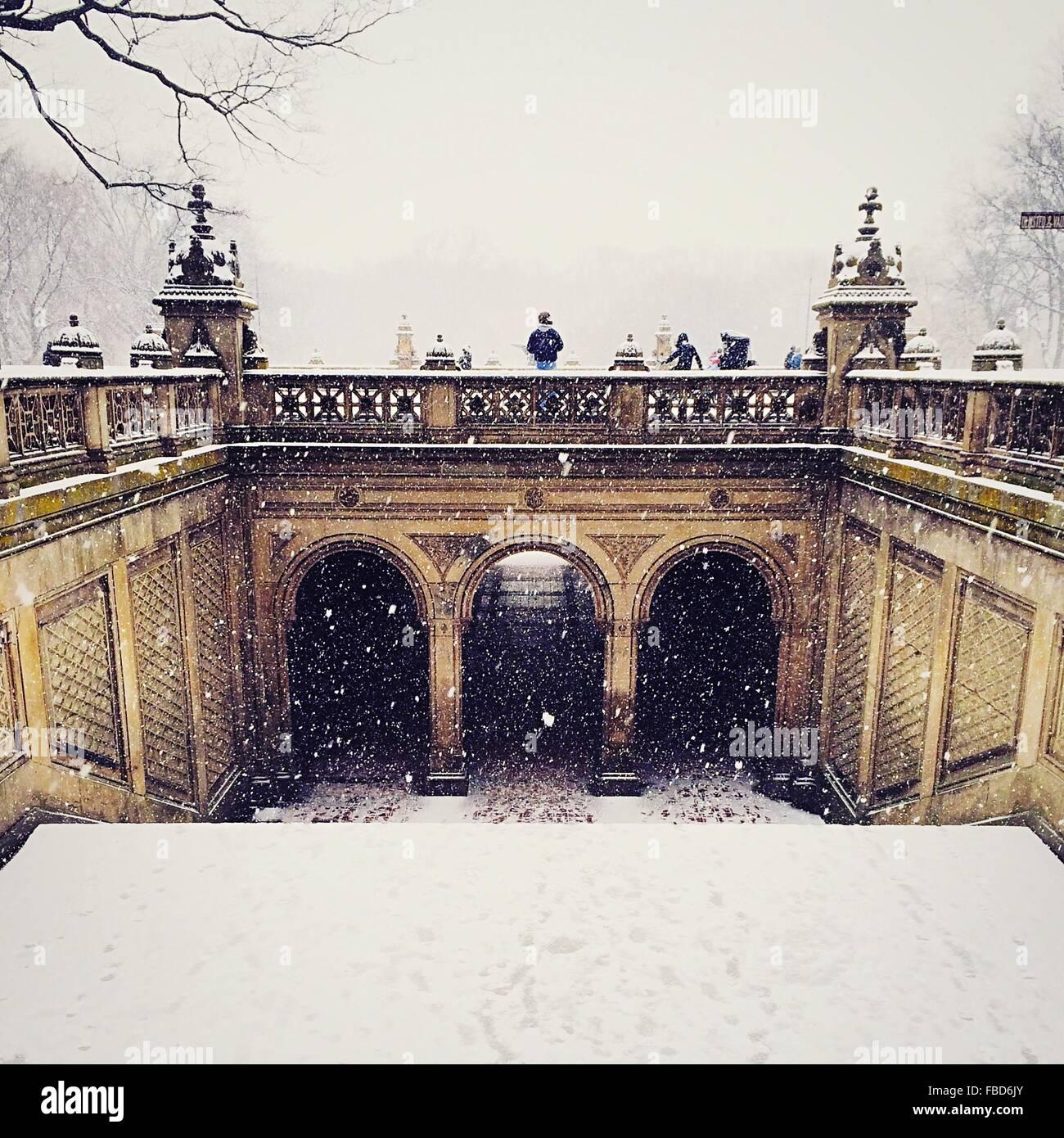 Les gens sur le pont par temps de neige contre Ciel clair Photo Stock