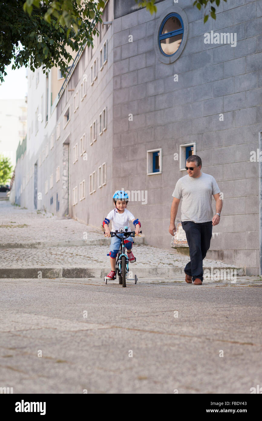 Man Looking At Boy Riding Bicycle In City Photo Stock