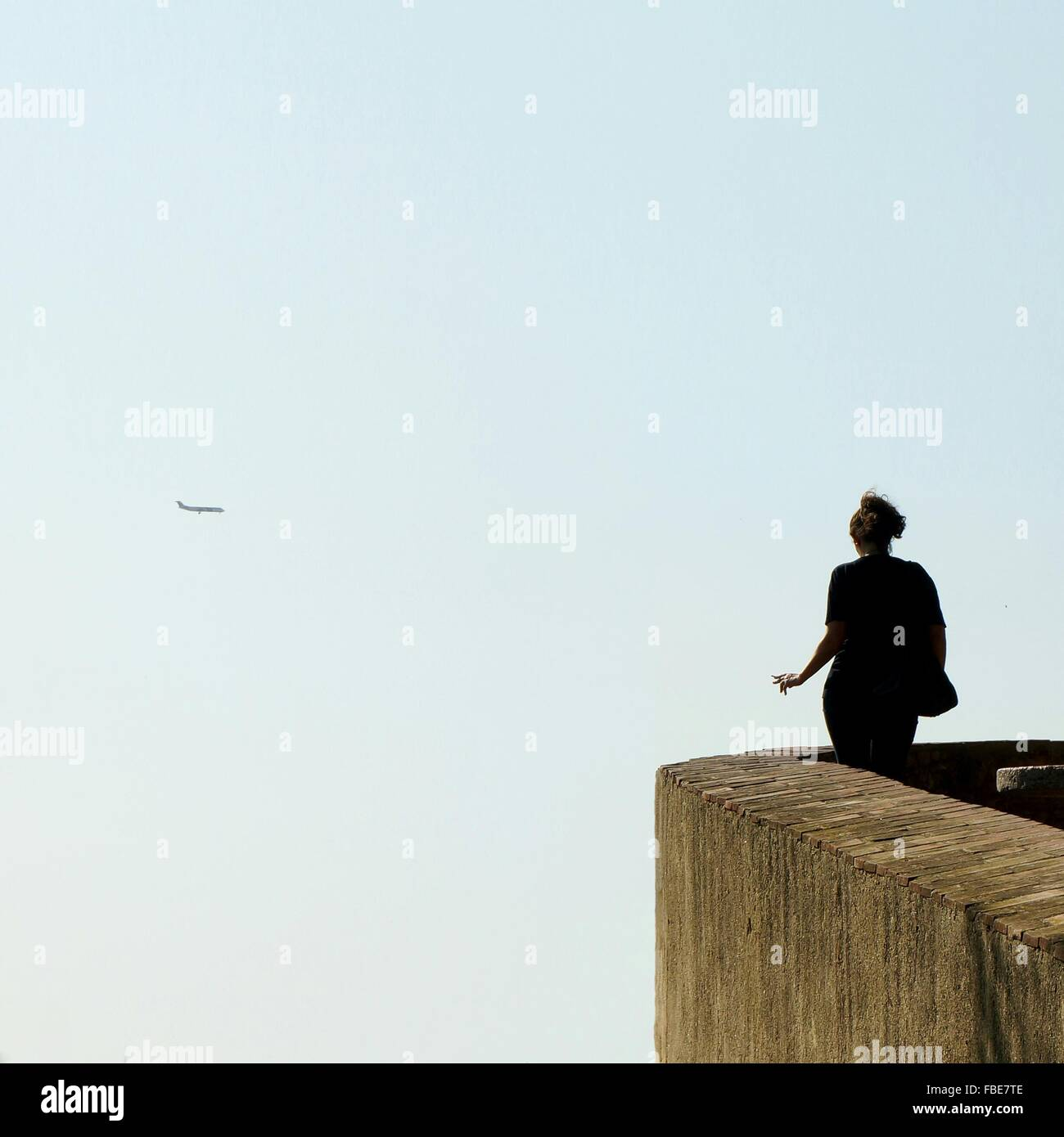 Vue arrière du Woman Looking At Airplane Flying Against Sky Photo Stock