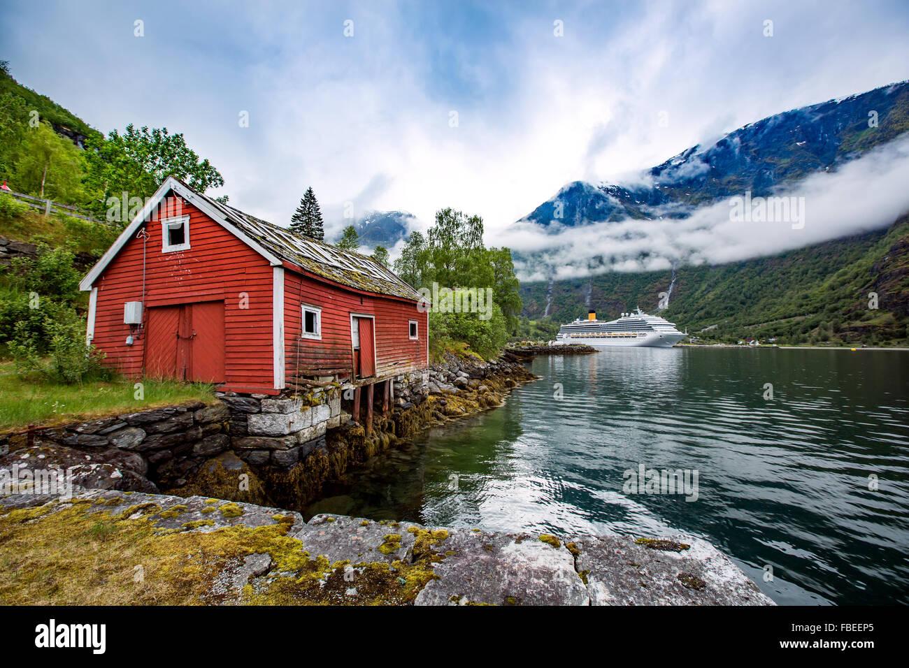 La Norvège paysage, la maison sur la rive du fjord dans l'arrière-plan d'amarrage bateau de croisière. Photo Stock