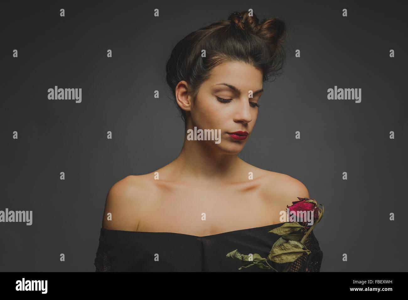 Beau jeune mannequin à la Rose Rouge à l'arrière-plan gris contre Photo Stock