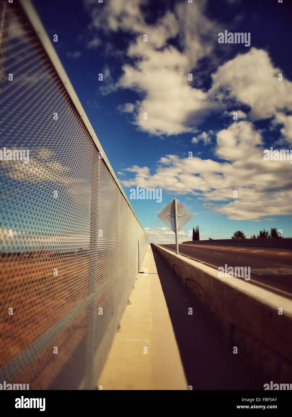 Sentier par une clôture contre Ciel nuageux Photo Stock