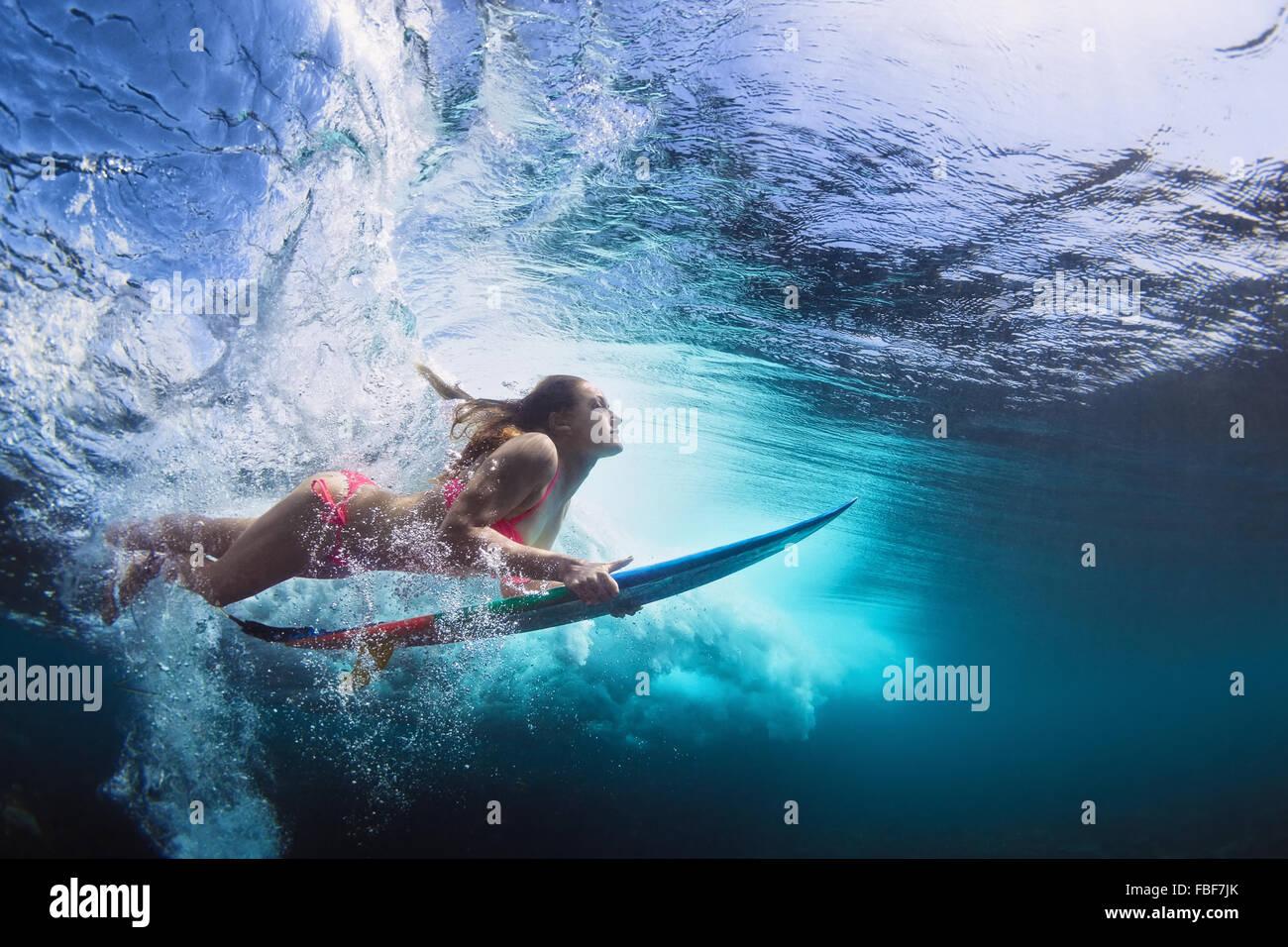 Jeune fille en bikini - surfer avec planche de surf sous l'eau plongée avec plaisir sous les grandes vagues Photo Stock