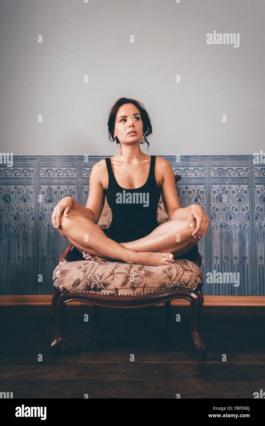 Jeune femme avec les jambes croisés assis sur un fauteuil contre le mur à la maison Photo Stock