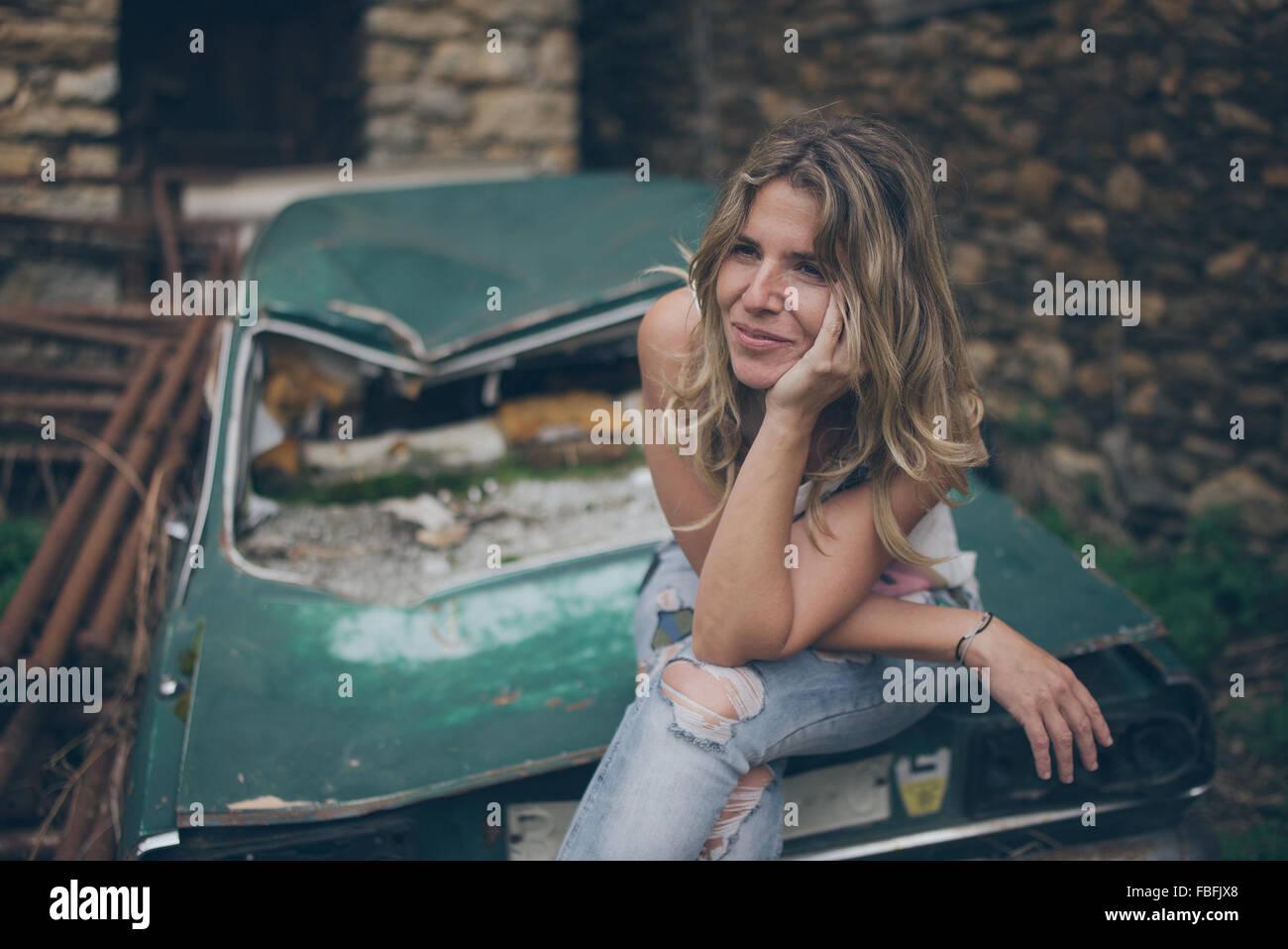 Jeune femme à l'écart tout en restant assis sur voiture abandonnée Banque D'Images