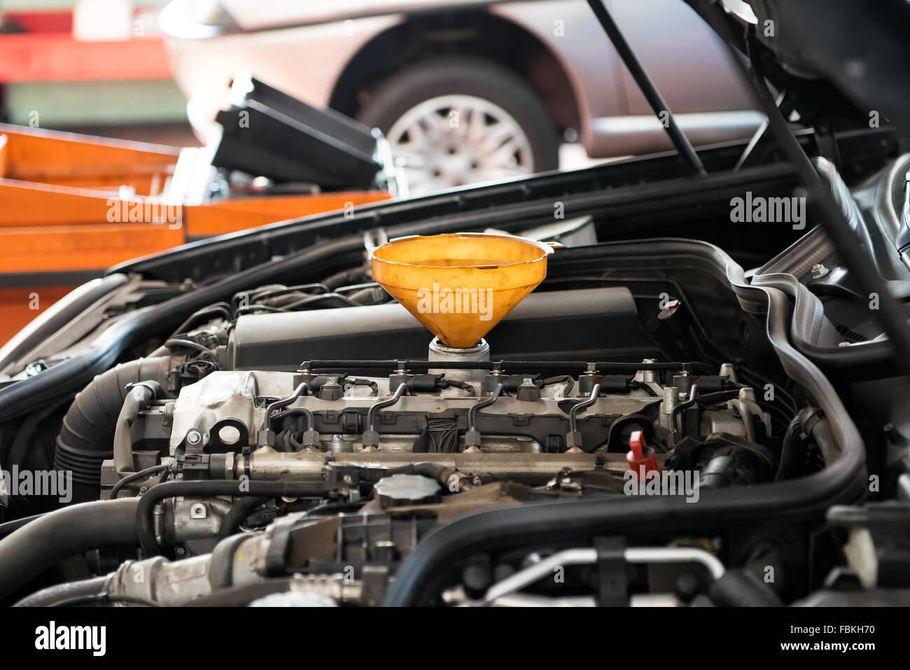 Entonnoir en plastique jaune pour jeter de l'huile placée dans le carter de moteur d'une voiture à Photo Stock