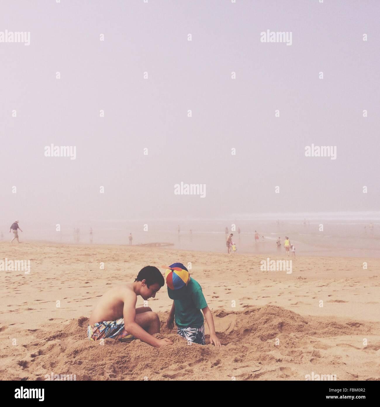 Deux garçons jouant avec le sable sur la plage Photo Stock