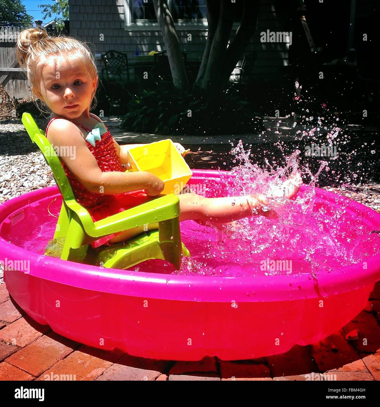 Vue de côté Portrait Of A cute girl aux projections d'eau dans la baignoire en plein air Photo Stock