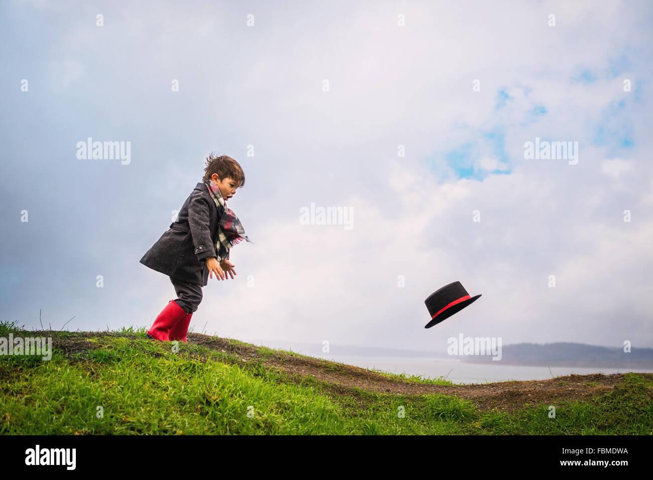 Garçon courir après son chapeau souffle loin dans le vent Photo Stock