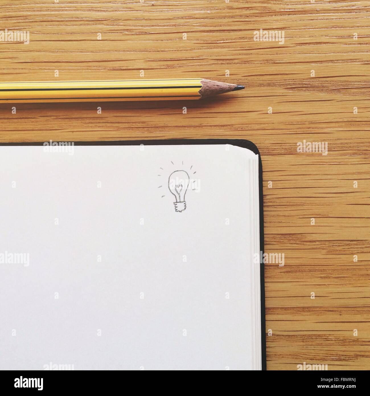 Journal dessiné sur l'ampoule par Crayon sur table Photo Stock