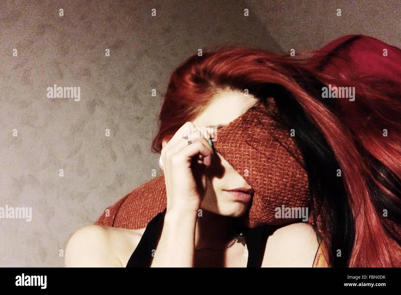 Jeune femme se reposer sur un canapé, tandis que Covering Face Photo Stock