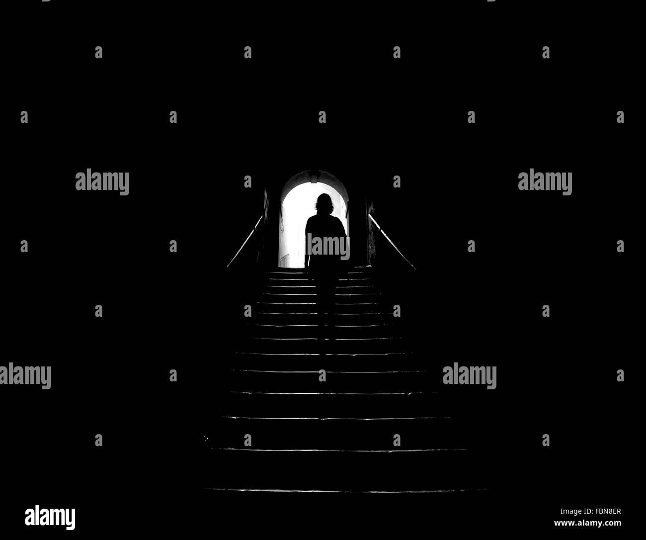 Vue arrière de Silhouette Femme en escalier dans Tunnel noir Photo Stock
