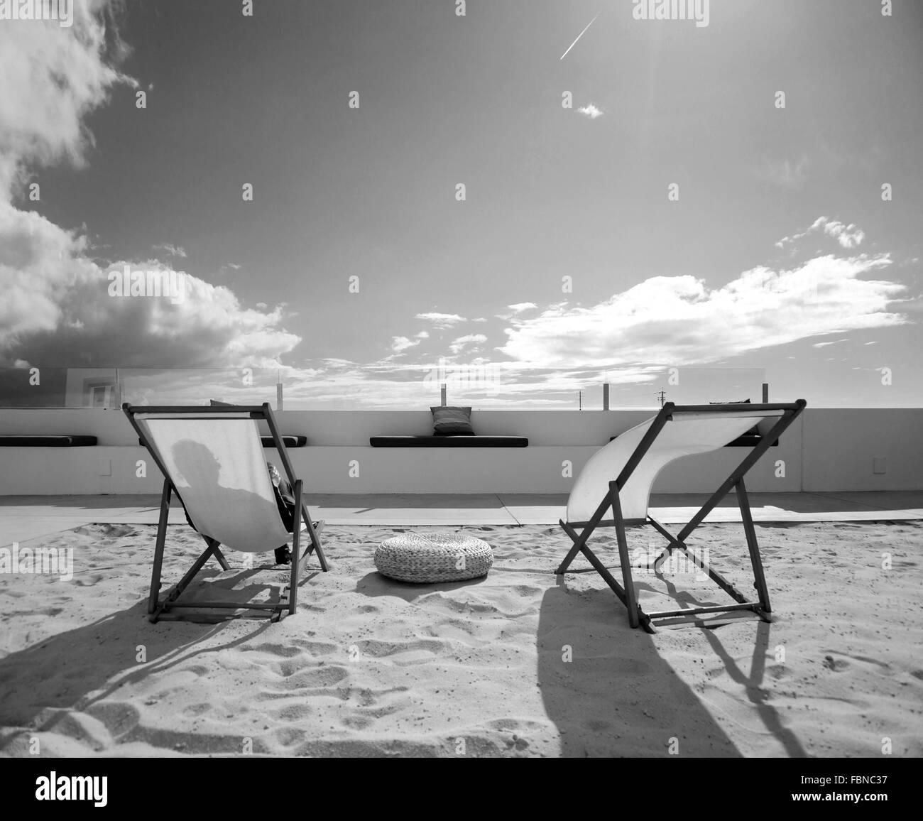 Des transats sur le sable contre ciel nuageux sur Sunny Day Photo Stock