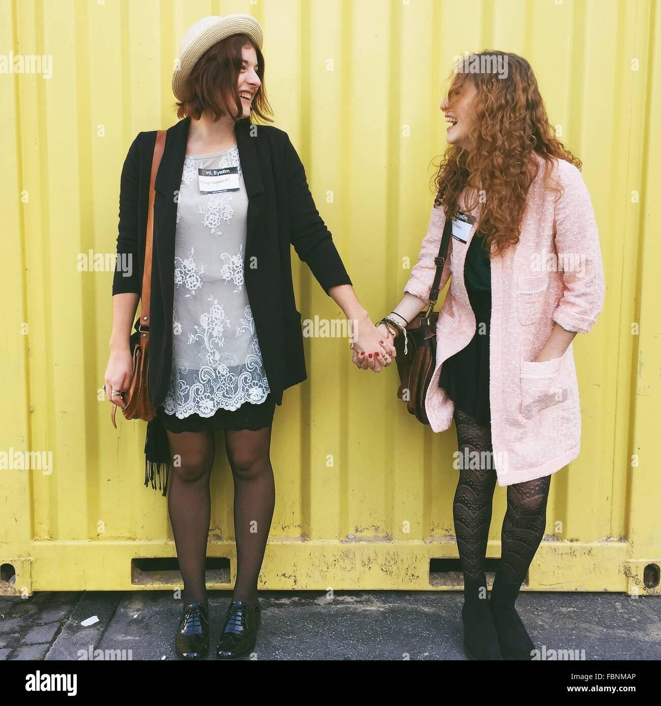 Joyeux ami tenant la main en position debout contre la paroi métallique Photo Stock