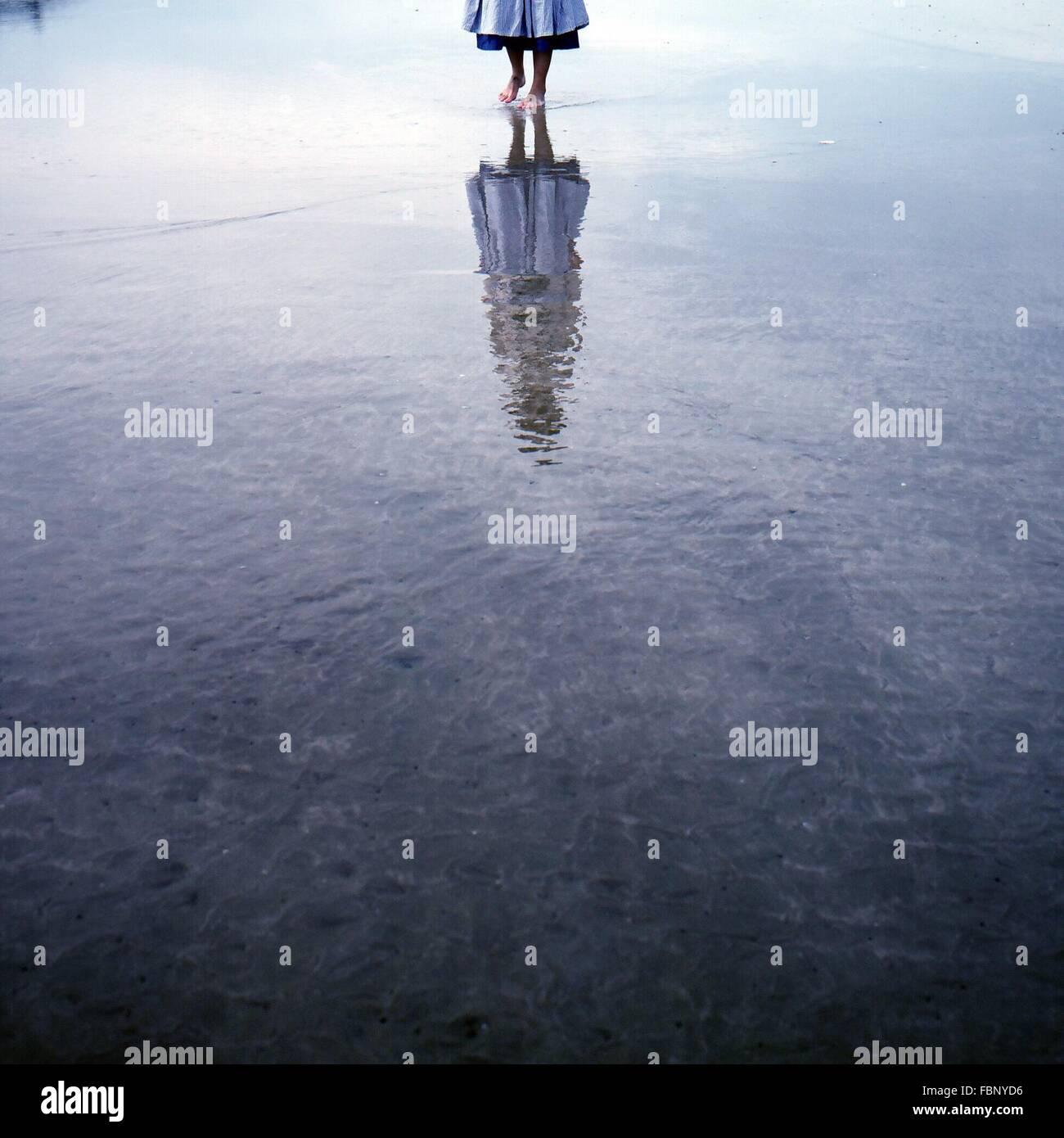 La section basse de la femme marche sur l'eau avec la réflexion Photo Stock
