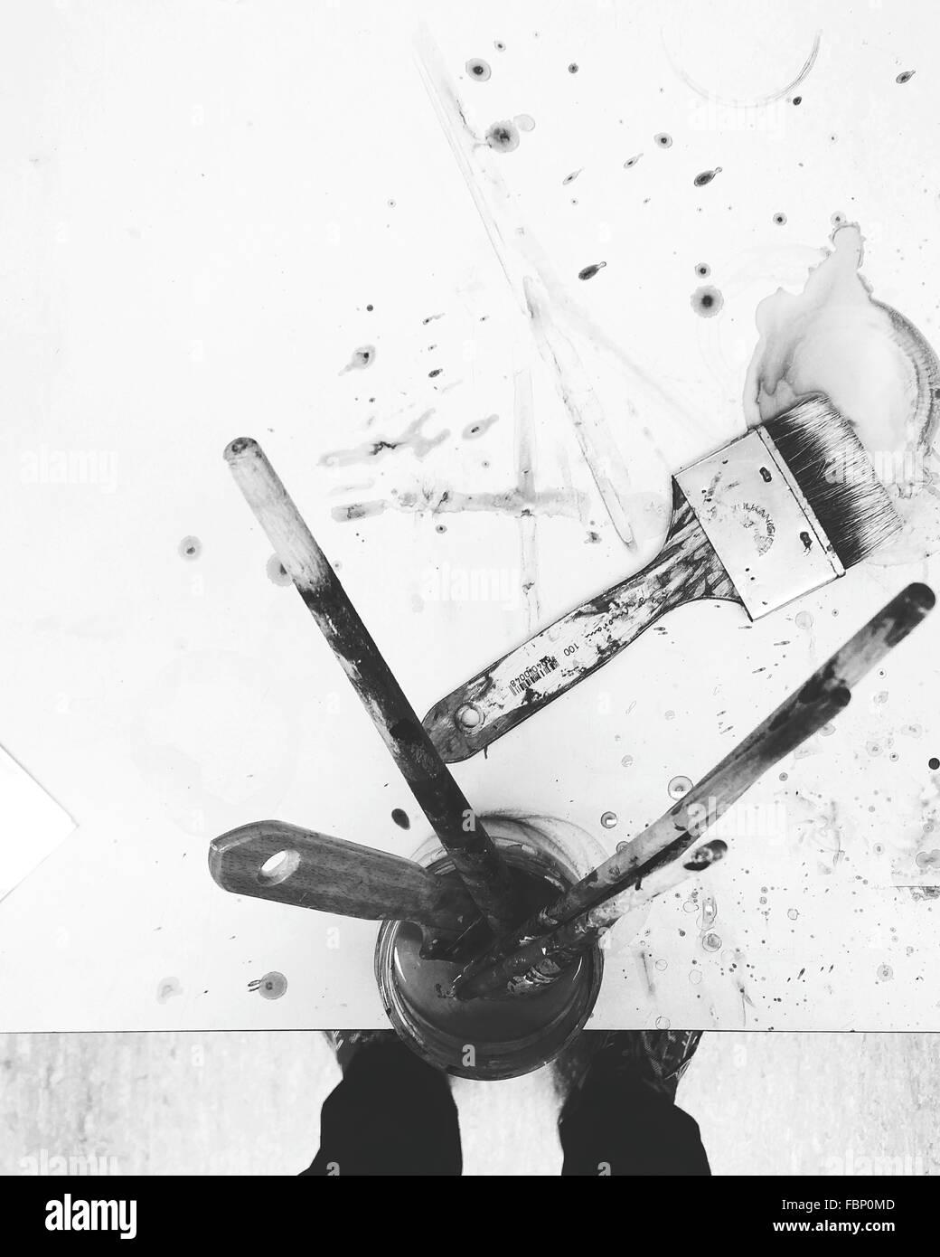 La section basse de l'Homme debout par l'équipement de peinture sur table Photo Stock