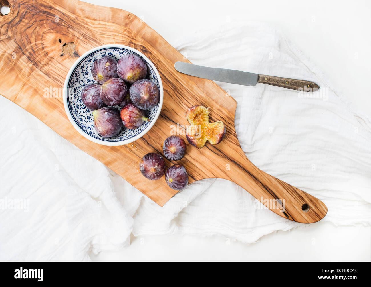 Figues fraîches en bleu Bol en céramique à motifs et sur bois d'olive sur fond blanc, vue du Photo Stock