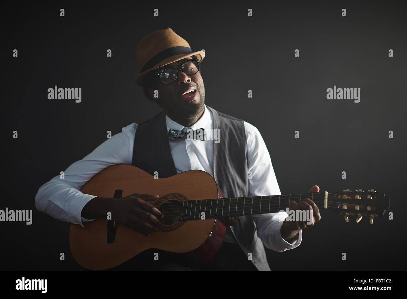 Jeune homme africain qui joue de la guitare et chant Photo Stock