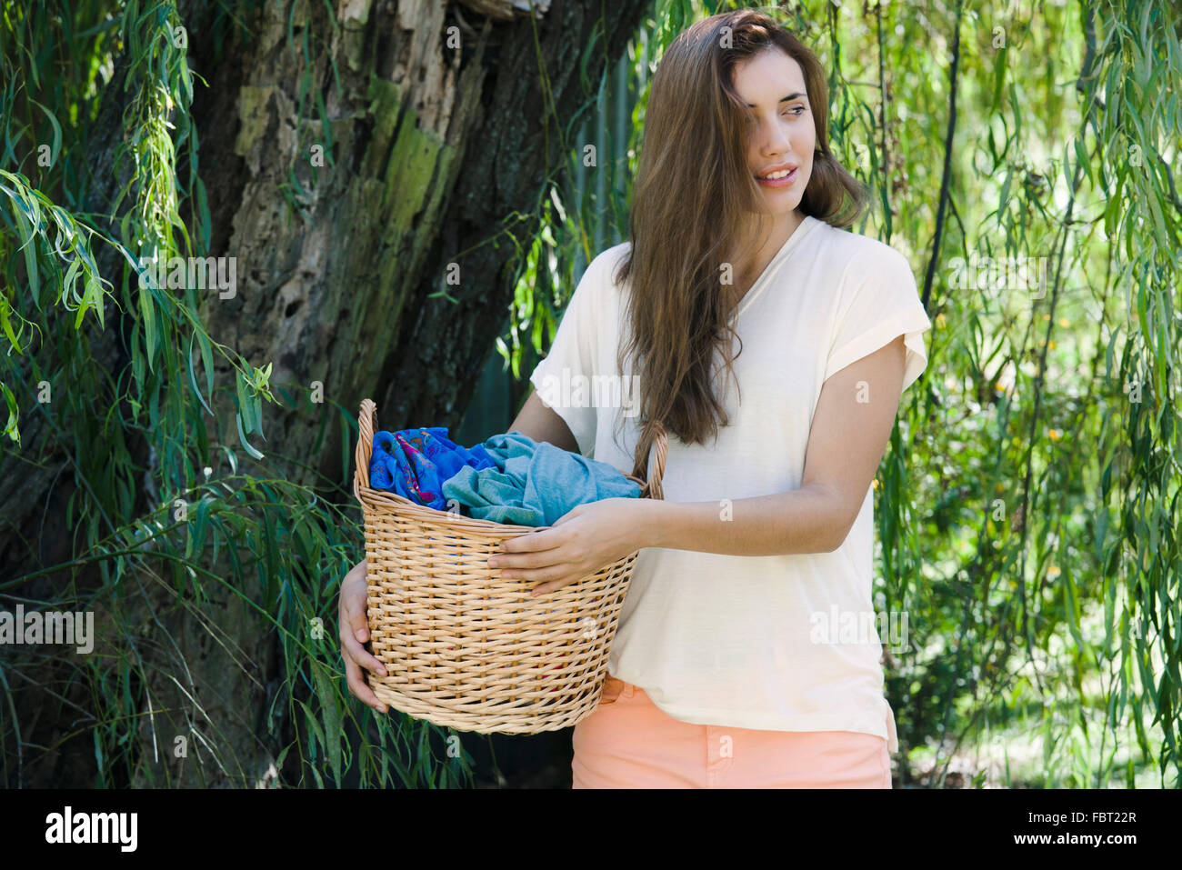 Woman carrying laundry basket Photo Stock