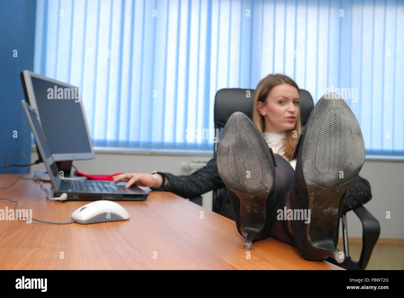 Business woman relaxing avec ses pieds sur le bureau banque d