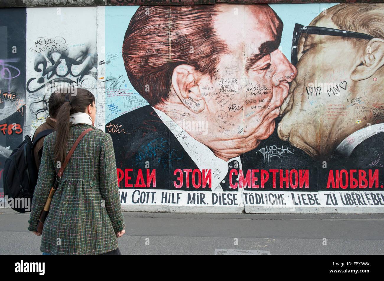 Les touristes de l'oeuvre d'affichage sur le mur de Berlin à l'East Side Gallery représentant un baiser entre Leonid Banque D'Images