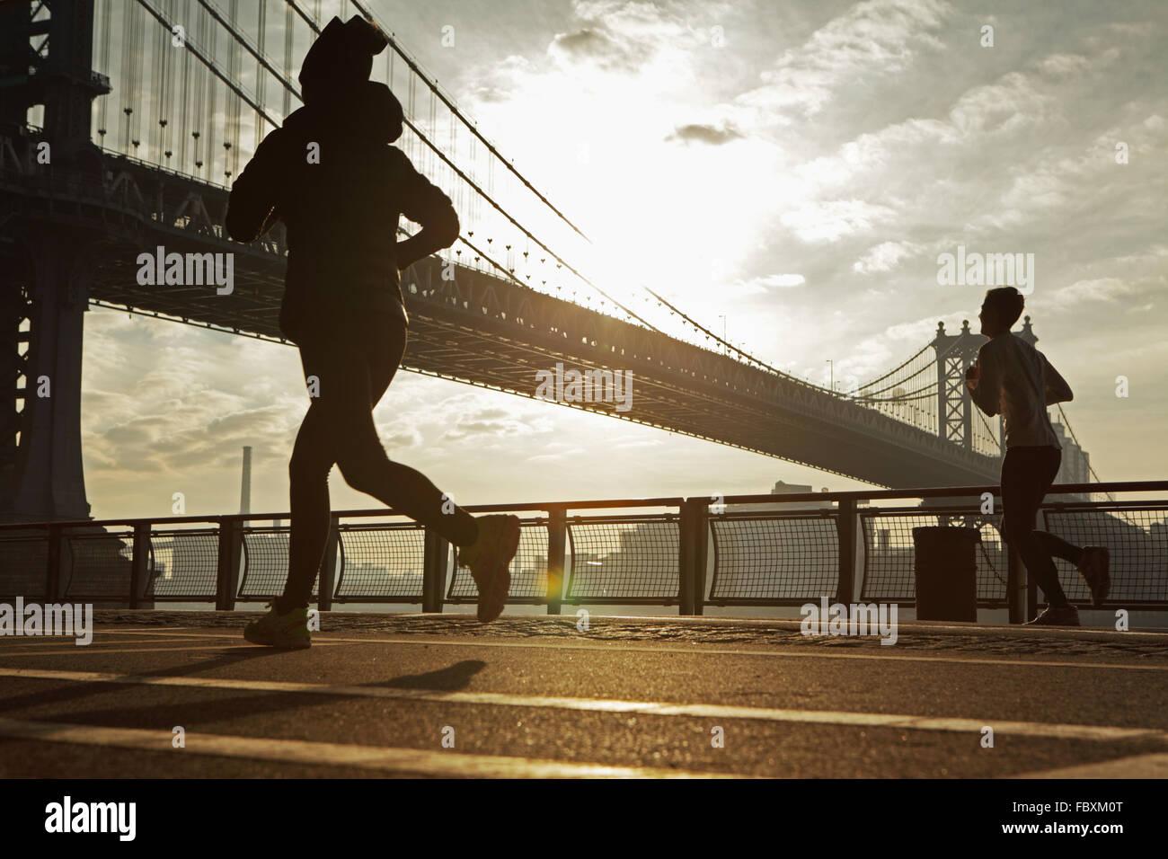Le lever du soleil sur le pont de Manhattan New York City matin comme deux joggeurs courir vers le nord jusqu'à Photo Stock