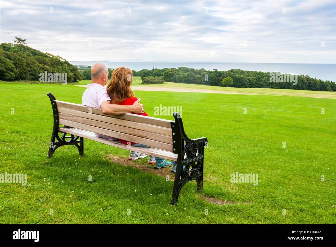 Vue arrière du moyen age couple assis sur un banc face à la mer Photo Stock